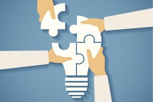 Vector concept of creative teamwork with light bulb puzzle and human hands